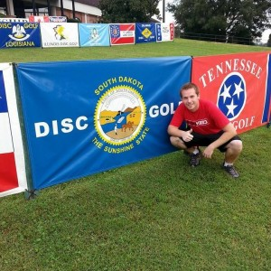 Sahr standing next to the South Dakota Disc Golf banner at the USDGC.