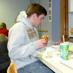 Junior Michael Lewis eats fast food while finishing up a project for class on Tuesday. Multi-tasking is an essential skill students must have in order to succeed in college.