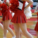 "South Sioux City boys' basketball cheerleaders' new uniforms have received varying feedback. ""The skirts used to be a lot longer,"" a veteran cheerleader in the stands said. ""I guess that'll get the crowd on her feet, though."" Here, cheerleaders pump up the crowd during a January 29th game."