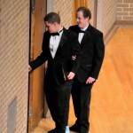 Eric Plemel leads Justin Dixson offstage. Dixson, a blind student, serves as a human pitch pipe for the choirs he sings in.
