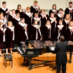 The College Choir claps along as Blair Remmers, bottom left, sings a gospel solo. The morning before the concert, the group traveled to South Sioux City, Nebr. to perform a set of religious songs.
