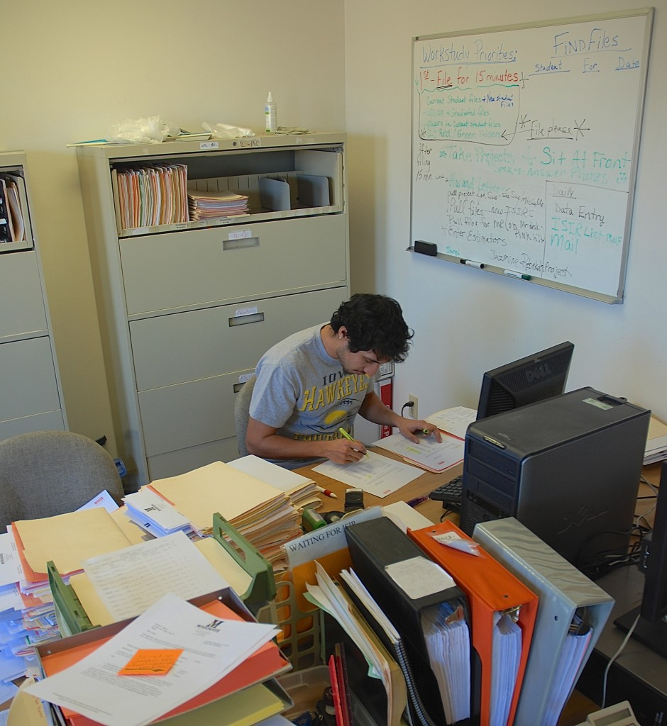 (College Life) Fernando Franco, a senior attending Morningside College, working his way through a stack of files at his work-study job on campus. Contact the Morningside Financial Aid Office today to learn if you qualify and possible openings on campus.